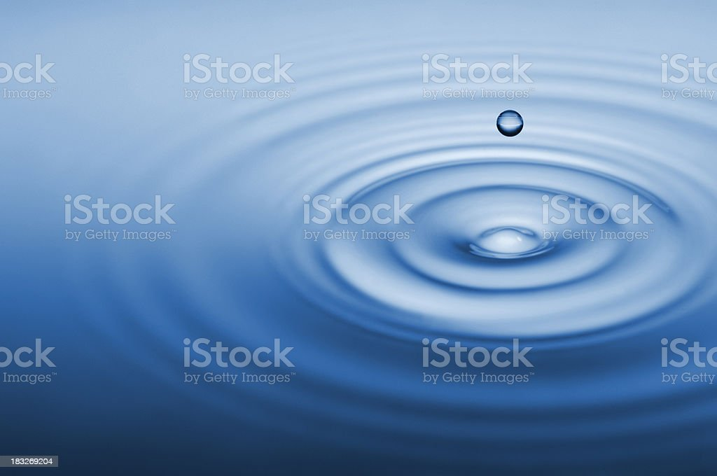 Droplet of water falling into pool emanating ripples royalty-free stock photo