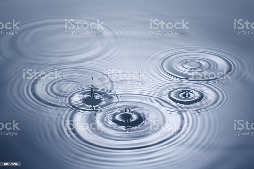 Droplets of water falling in to blue pool stock photo