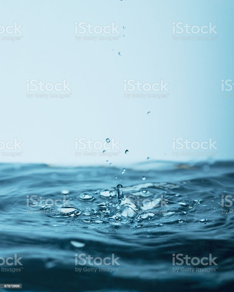Droplets splashing in pool of water royalty-free stock photo