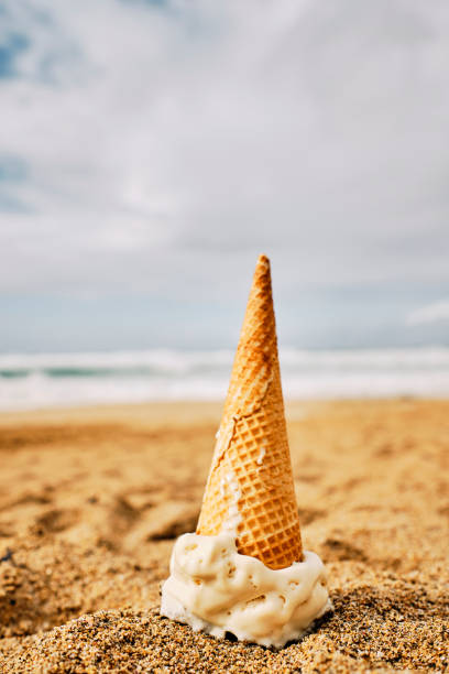 dropped ice cream cone face down in the sand, beach holiday accident. - ice cream cone stock pictures, royalty-free photos & images