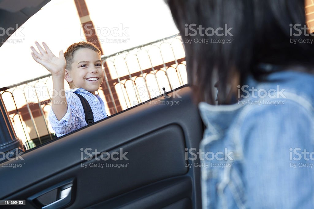Dropped off at school, boy waves to mom stock photo