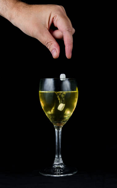 dropping a pill into wine - 殺球 個照片及圖片檔