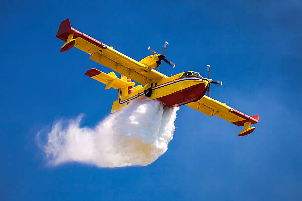 Dropping water A twin-engined water bomber dumping water in the air smoke jumper stock pictures, royalty-free photos & images