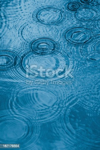 Close up of a water surface with rain drops falling.Monochrome blue