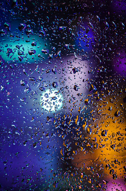 Drops of night rain on window, abstract background