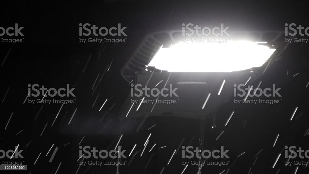 Drops of rain at night under street led light. Abstract background