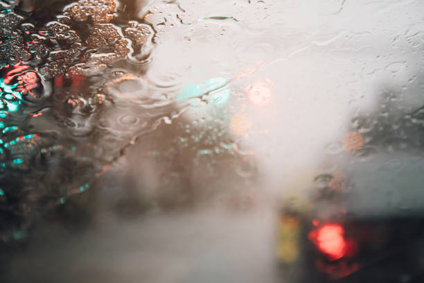 Drops Of Rain Drizzle on the glass windshield in the evening. street in the heavy rain. Bokeh Tail light. soft Focus. Please drive carefully, slippery road. soft focus. stock photo
