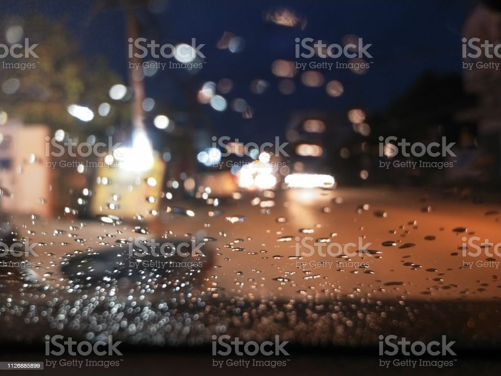 Drops of rain from the rain on the car glass during the night. Bokhen...
