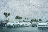 Drops of rain on the window; parked cars in the background; shallow depth of field