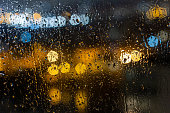 istock Drops of rain on window blured citylights at night 1310840499