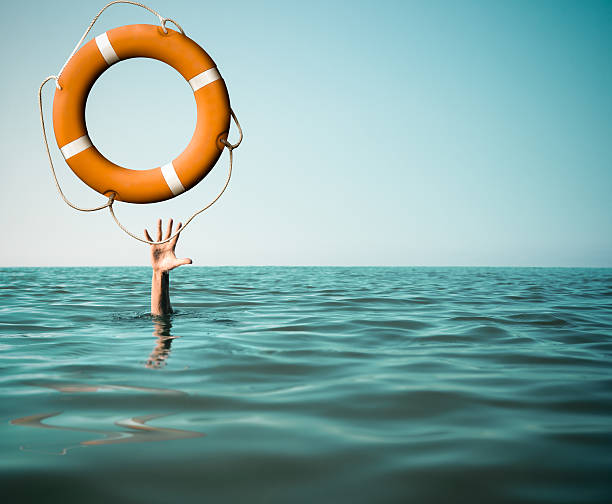 Drown man with rised hand getting lifebuoy help in sea Drown man with rised hand getting lifebuoy help in sea or ocean weakness stock pictures, royalty-free photos & images