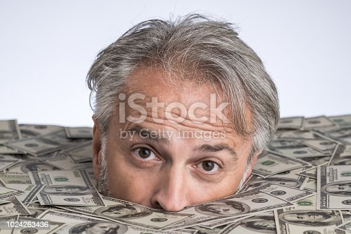 Senior man drowning in money
