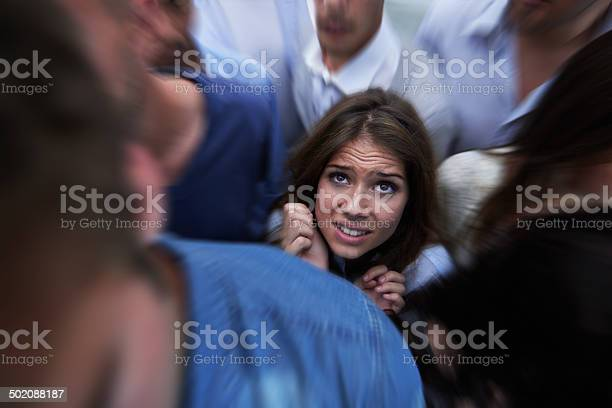Shot of a fearful young woman feeling trapped by the crowd