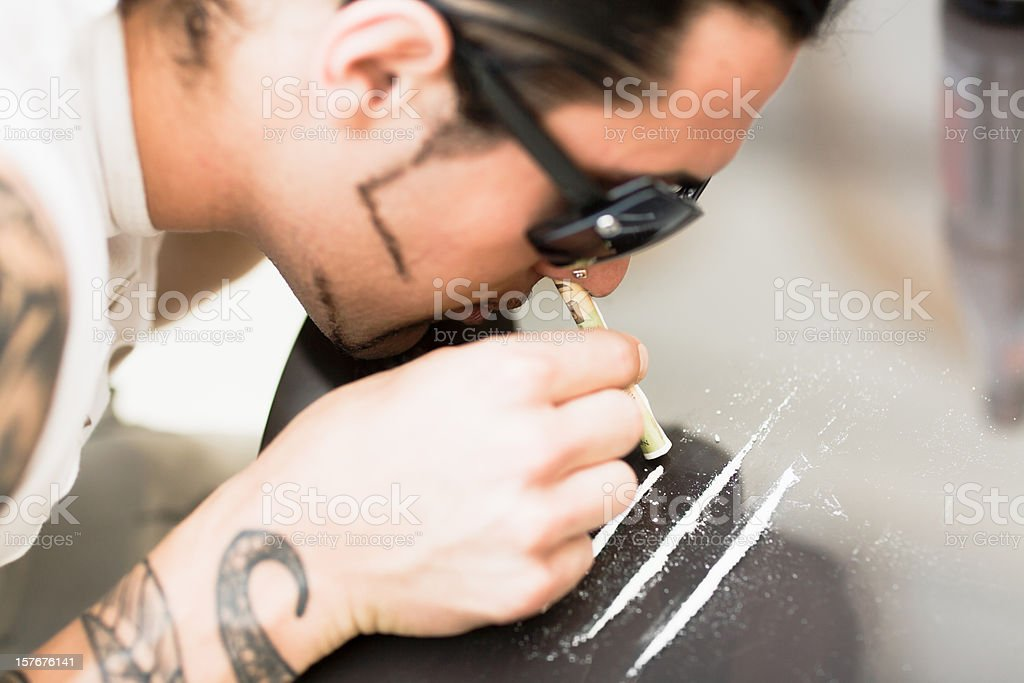 Drug Abuse Young man doing Cocaine stock photo