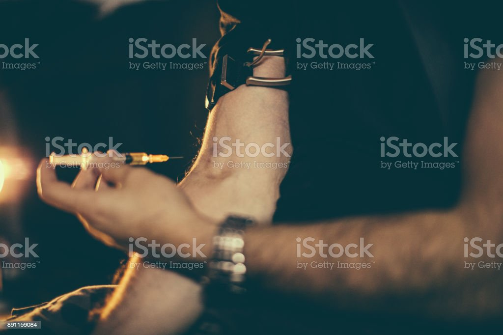 Drug addict injecting heroin into arm stock photo