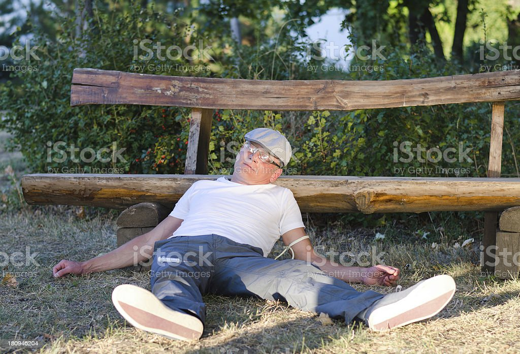 Drug addict lying in a park royalty-free stock photo