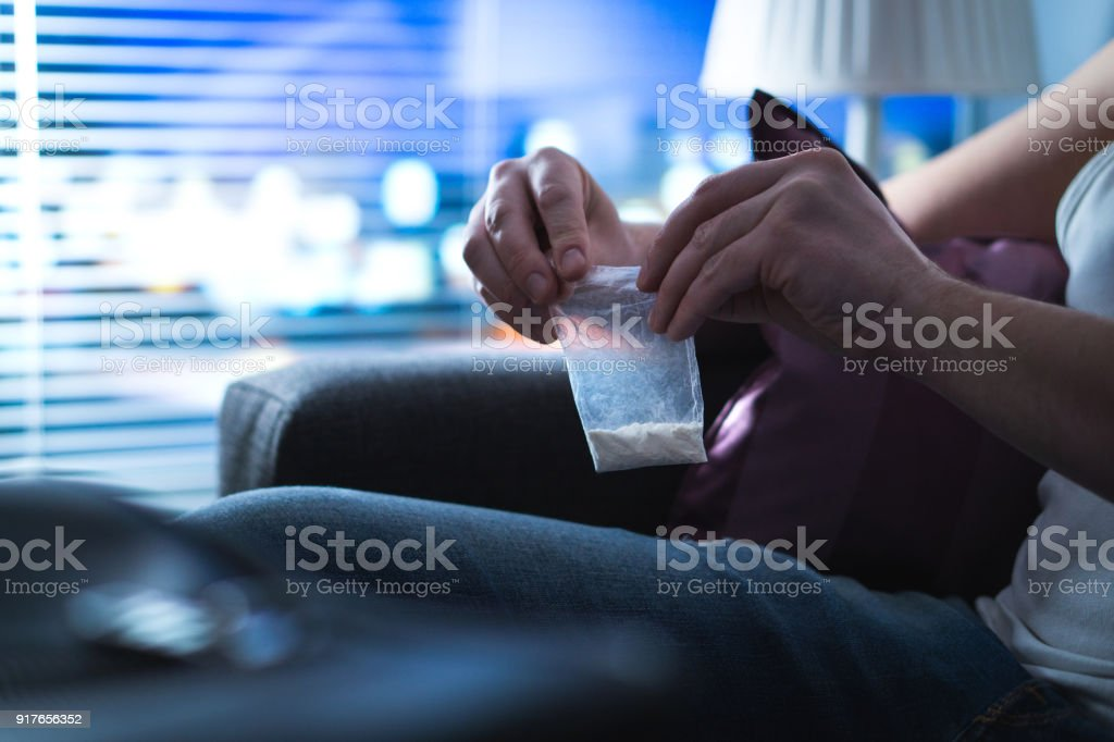 Drug addict or dealer closing bag of cocaine. Young man holding bag of white powder late at night. Narcotic abuse or dealing. stock photo