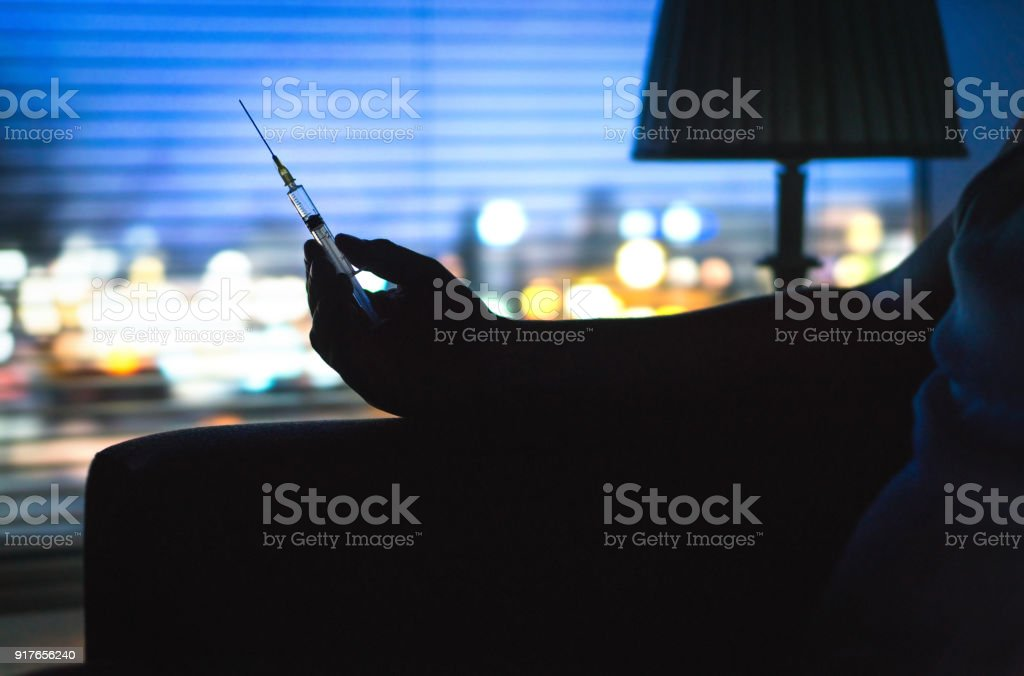 Drug addict with heroin syringe silhouette in dark. Hand holding needle late at night. stock photo