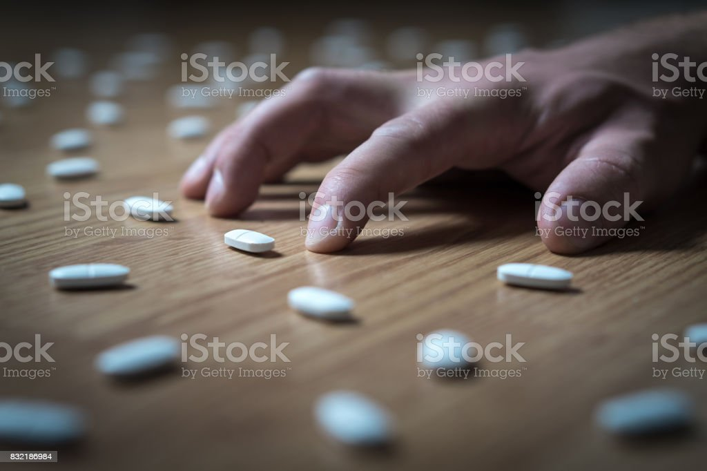 Drug addict with withdrawal symptoms lying on floor. Drug addiction, medical abuse and narcotics hook and dependence concept. Tablet overdose. Depression and problem. Hand surrounded by many pills. stock photo