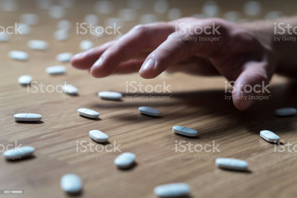 Drug addict with withdrawal symptoms reaching out to many pills on the floor with hand. Drug addiction, medical abuse and narcotics hook and dependence concept. Tablet overdose. stock photo
