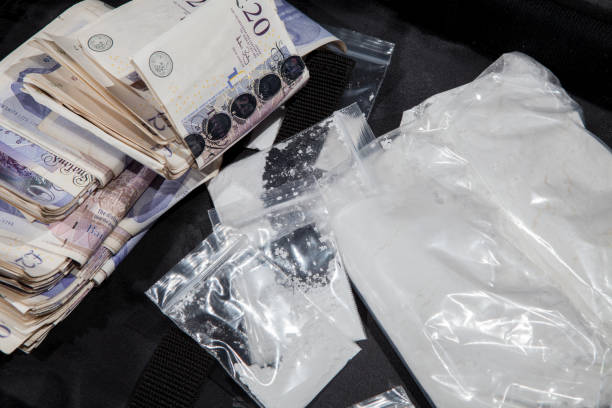 UK drug crime. Cash and cocaine. A dealers cash from selling illegal drugs. UK drug crime. Cash and cocaine. A dealers cash from selling illegal drugs. White powder in bags with substantial amount of money. drug cartel stock pictures, royalty-free photos & images