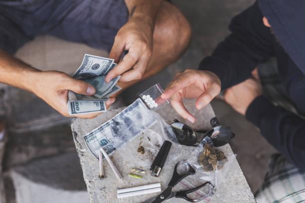 Drug dealer selling ecstasy Drug dealer selling ecstasy pills to a drug addict drug cartel stock pictures, royalty-free photos & images