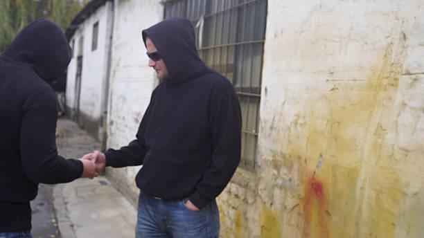drug dealer selling portions of heroine - camello fotografías e imágenes de stock