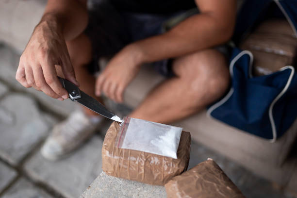 Drug dealer testing drug purity Drug dealer testing heroin purity and preparing goods for trafficking, packing cocaine bricks, pills and marijuana. Focus on the tip of the knife switchblade stock pictures, royalty-free photos & images