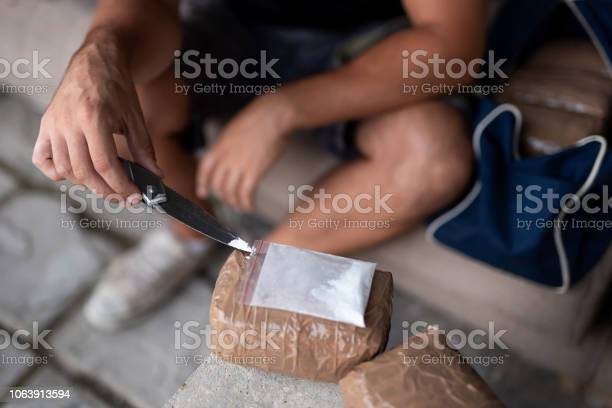 Drug dealer testing drug purity Drug dealer testing heroin purity and preparing goods for trafficking, packing cocaine bricks, pills and marijuana. Focus on the tip of the knife Addict Stock Photo