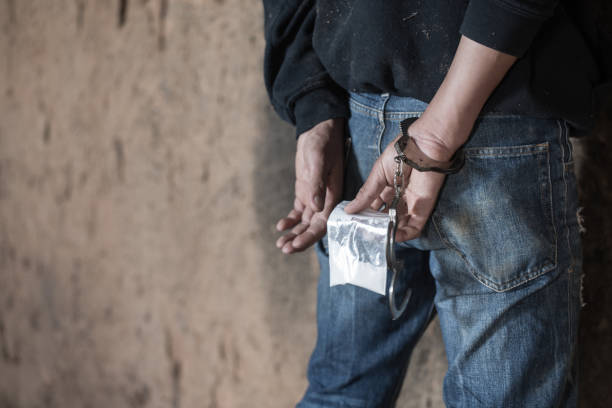 Drug dealer under arrest confined with handcuffs along with heroin,  Law and police concept.  World Anti-drug Day Drug dealer under arrest confined with handcuffs along with heroin,  Law and police concept.  World Anti-drug Day smuggling stock pictures, royalty-free photos & images