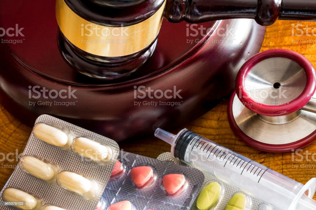 Drug law concept. Judges gavel with  stethoscope  and pills close up royalty-free stock photo