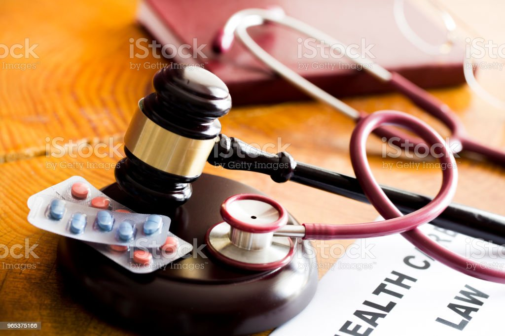 Drug law concept. Judges gavel with  stethoscope  and pills close up zbiór zdjęć royalty-free