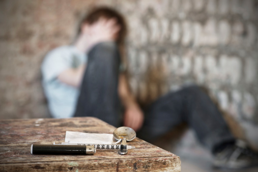 istock Drug paraphernalia with blurred addict behind 185327528