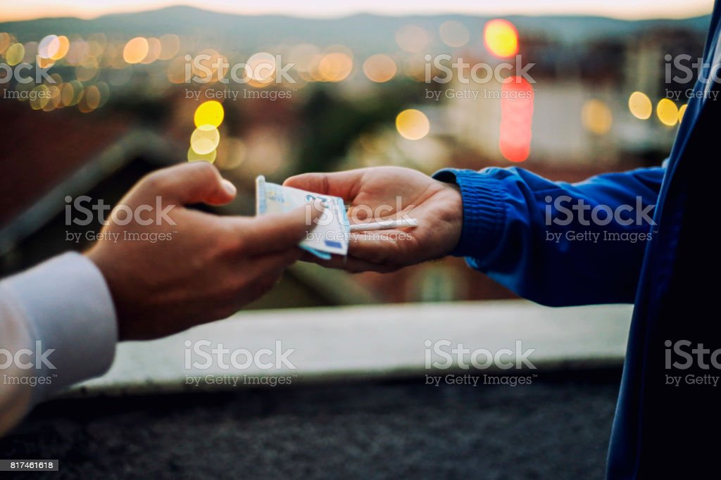 Drug sale and smoking concept - close up of marijuana joint and money stock photo
