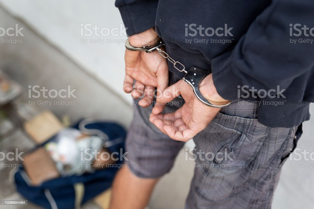 Drug smuggler under arrest stock photo