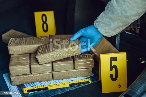 Packages of narcotics in car trunk. Drug smuggling.