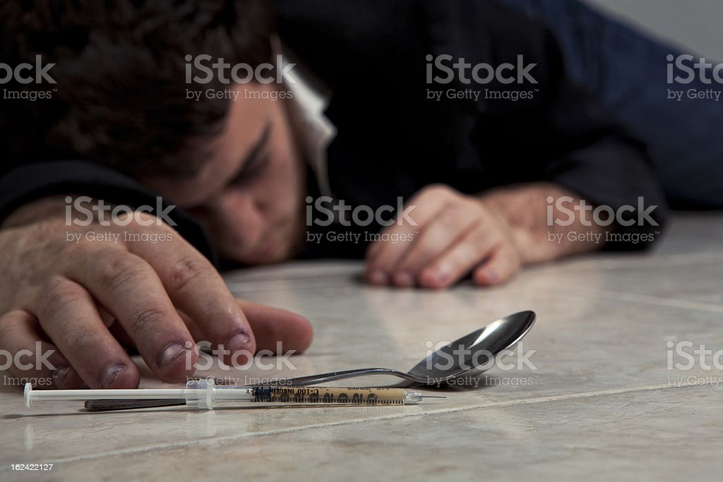 Drug syringe and spoon on the floor with dead male victim royalty-free stock photo
