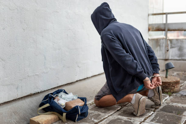 Drug trafficker under arrest Drug trafficker under arrest confined with handcuffs kneeling on the floor. Focus on the confiscated goods in the duffle bag smuggling stock pictures, royalty-free photos & images