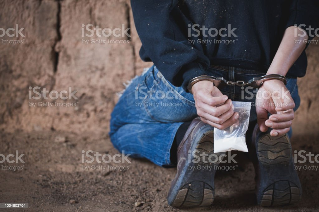 Drug traffickers were arrested along with their heroin. Police arrest drug trafficker with handcuffs. Law and police concept,26 June, International Day Against Drug Abuse and Illicit Trafficking stock photo