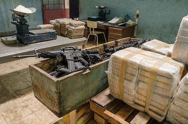 Drug warehouse This scene was staged to recreate an illegal warehouse. Weapons are movie props fake guns. Cocaine bricks resemble true smuggling merchandize smuggling stock pictures, royalty-free photos & images