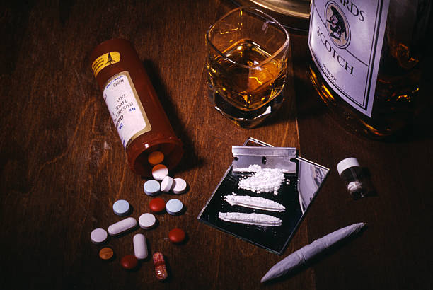 Drugs and Alcohol Addiction Tableau of drugs- pills, coke, marijuana, and alcohol. cocaine stock pictures, royalty-free photos & images