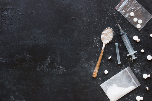 istock Drugs in the form of powder and tablets, a spoon and a syringe on a black background mockup 691978916