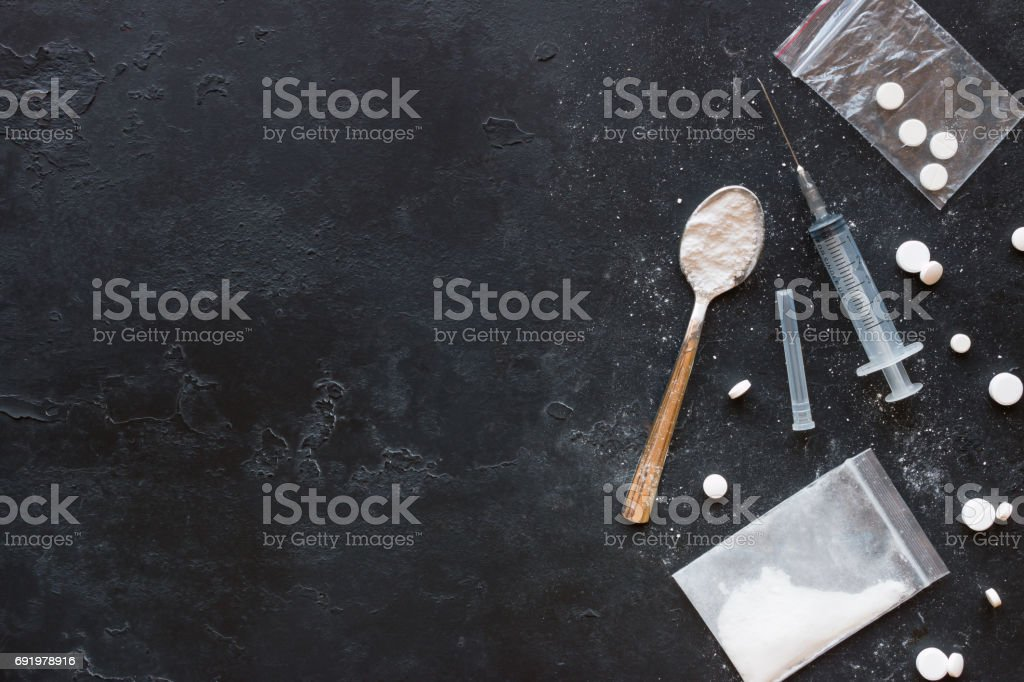 Drugs in the form of powder and tablets, a spoon and a syringe on a black background mockup stock photo