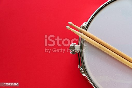 Drum and drum stick on red table background, top view, music concept