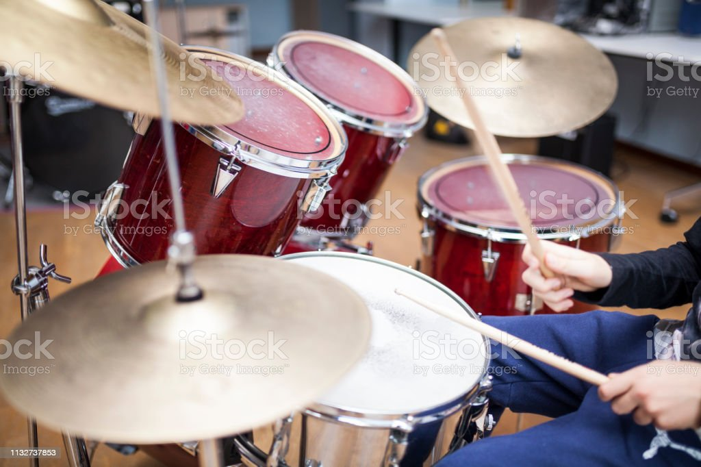 unrecognizable boy attending a drum class and playing