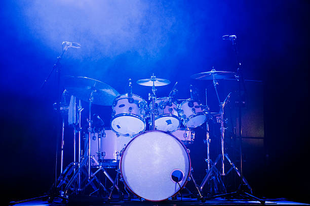 Drum Kit Full rock drum kit on stage with blue lighting and no drummer drum kit stock pictures, royalty-free photos & images