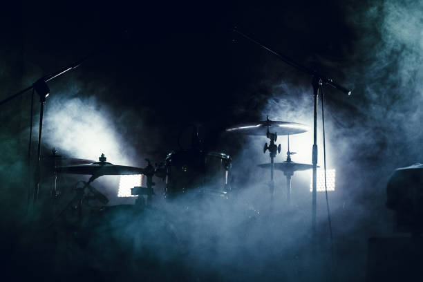 drum set in smoke on a stage - punk music stock photos and pictures
