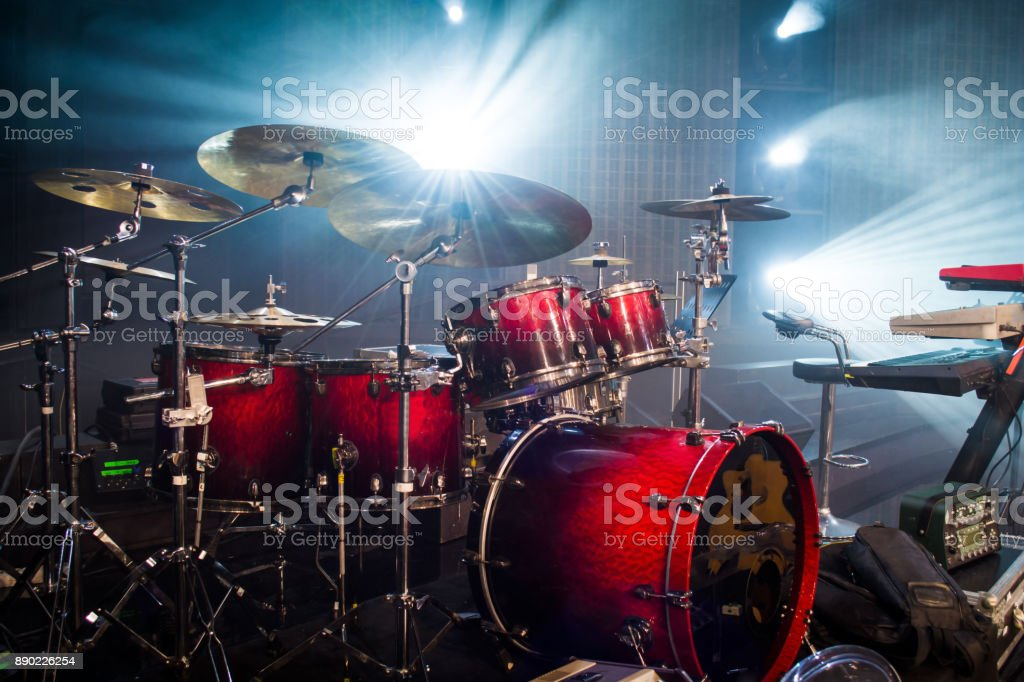drum set on stage and light background; empty stage with instruments...