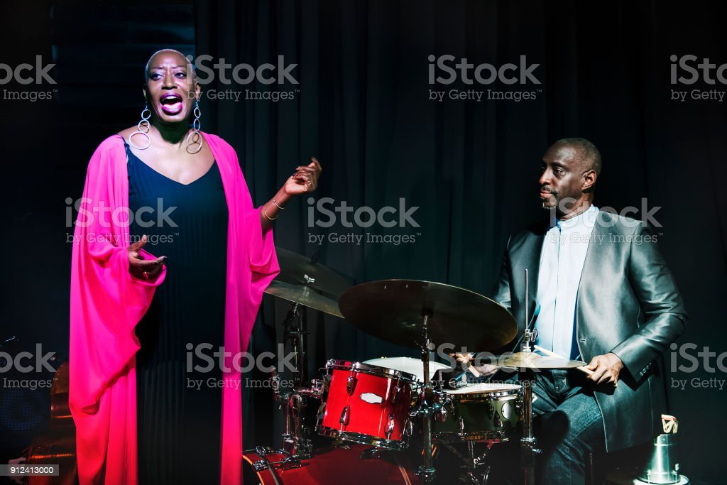 Drummer and singer performing in an event stock photo