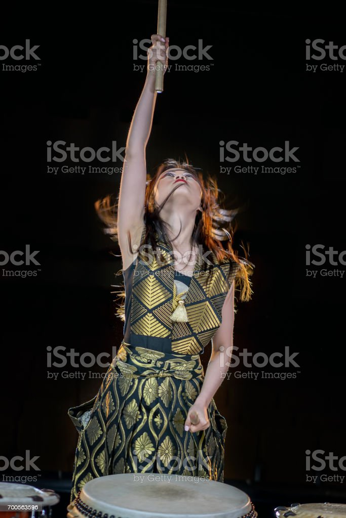 Drummer girl developing in the wind with loose hair looking up on a dark background stock photo